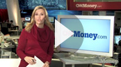 Newscaster stands near monitor that displays 'CNNMoney.com' - 'Play' arrow is superimposed over photo.